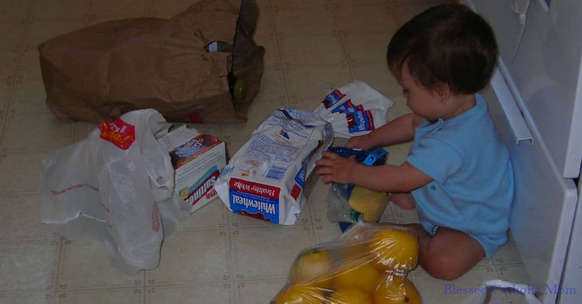 Image of a toddler boy sitting on the kitchen floor helping to unload grocery bags.