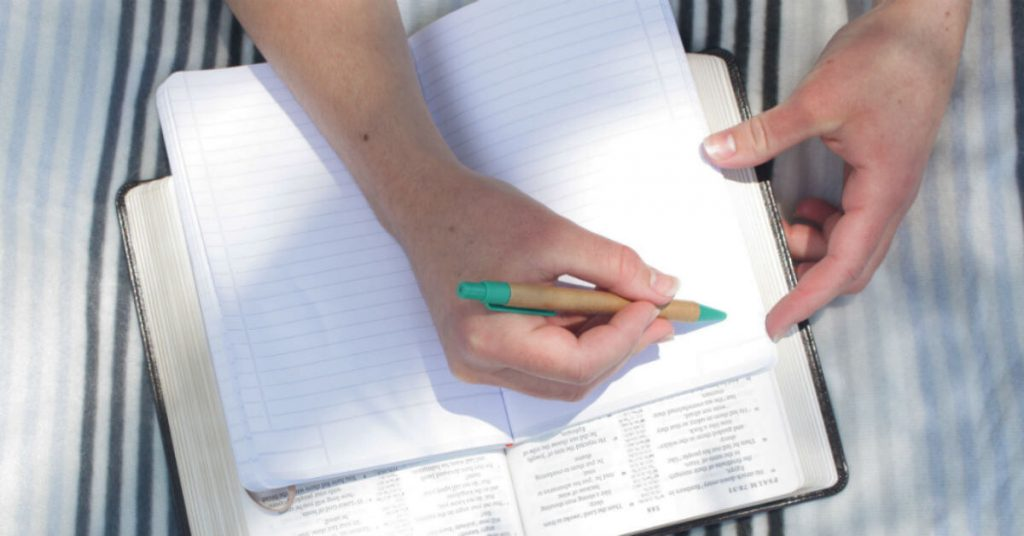 Image of two hands holding an open notebook on top of a Bible and one hand holds a pen and writes down notes.
