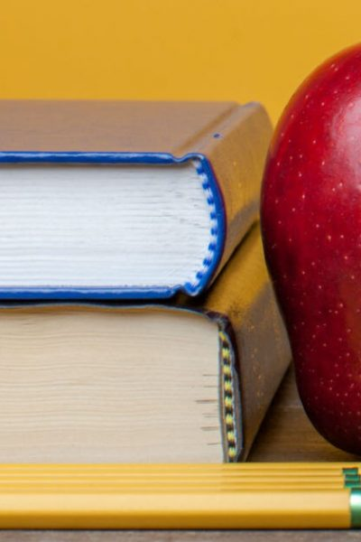 Discern if you are called to homeschool your children. Image of a stack of two books with three pencils and a red apple. Image from lightstock.com.