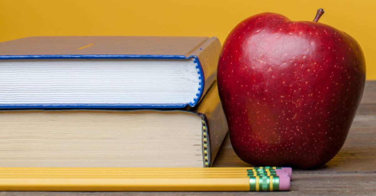 Image of a stack of two books with three pencils and a red apple. Image from lightstock.com.