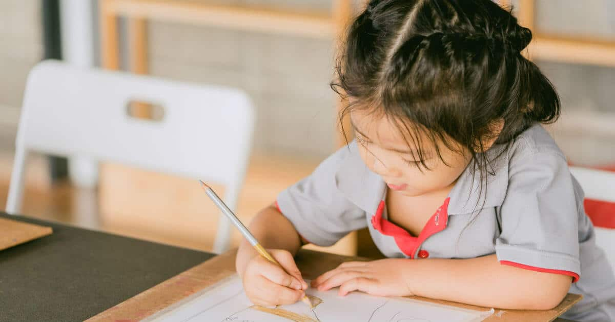 Get ready for a great school year! Image of a girl drawing with colored pencils at a desk or table.