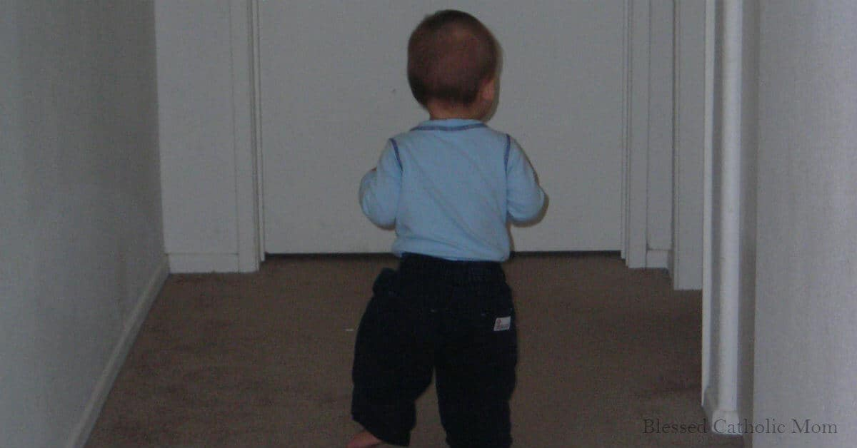 Image of a toddler boy walking down a hallway.