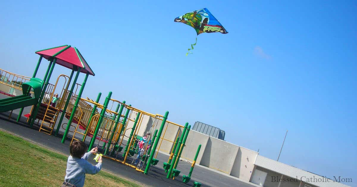Have fun as a family getting out of doors. Image of a boy flying kite at playground.