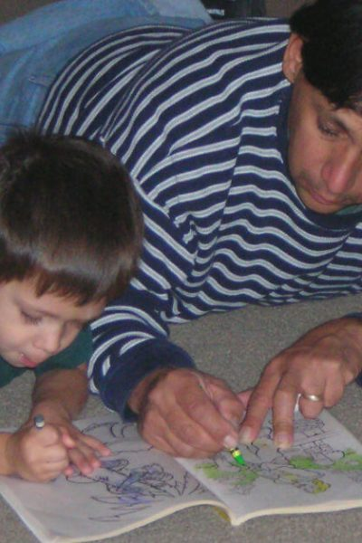 Plan kids date nights with your children. Image of young boy and his father laying on the floor coloring in a coloring book.