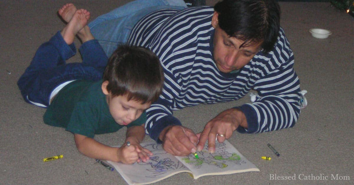 Image of a young son and father laying on the floor coloring in a coloring book.