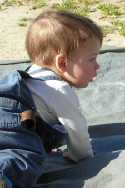Keeping track of kids' milestones is not as difficult as it may seem. Image of a toddler crawling outside.