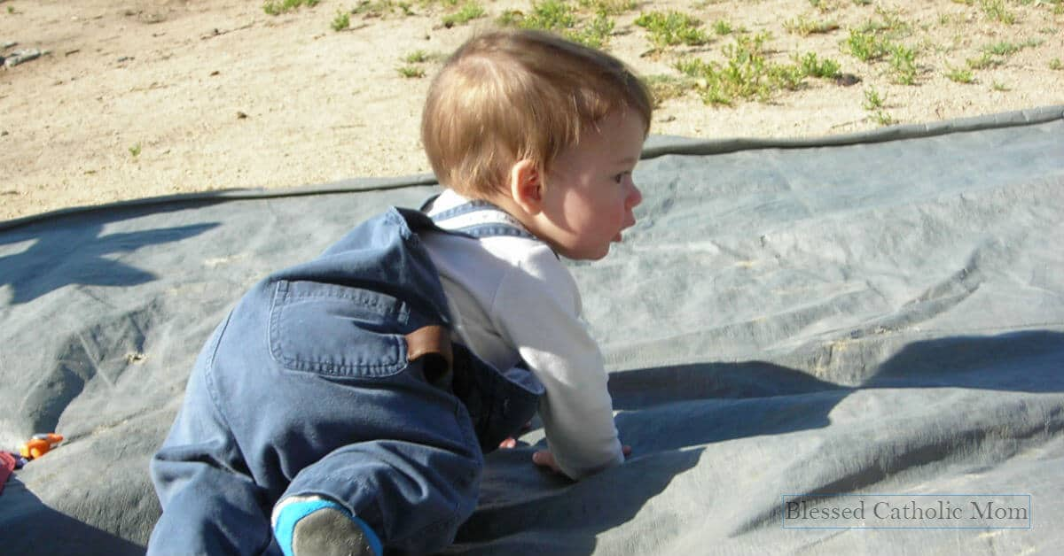 Image of a toddler boy crawling on tarp outside.