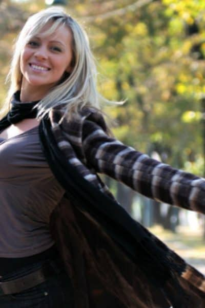 Image of a woman standing in a park, arms outstretched and smiling at the camera.