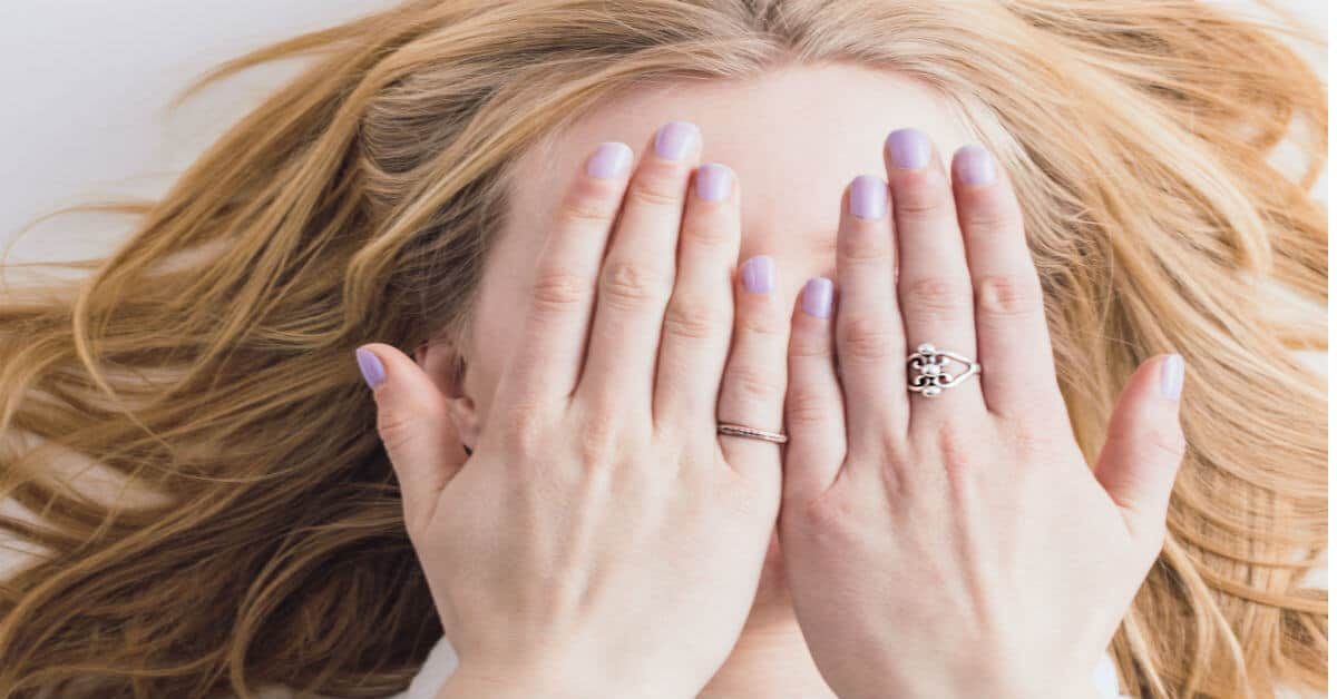 Image of a woman wearing 2 rings covering her eyes with her hands. Image from death to stock photo.
