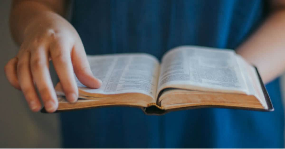 Image of hands holding Bible and about to turn the page. Image from lightstock.com.
