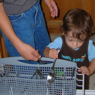 Establishing chores for kids is fairly simple. Image of a toddler boy helping his older brother unload the dishwasher.