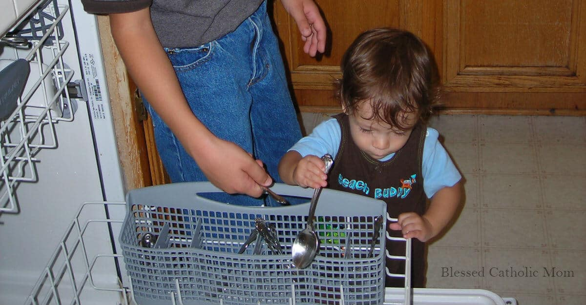 Image of a toddler boy helping his older brother unload the dishwasher.