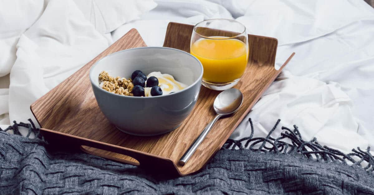 Image of a breakfast tray on a bed that contains a glass of orange juice, a bowl with yogurt, granola, and blueberries, and a spoon.
