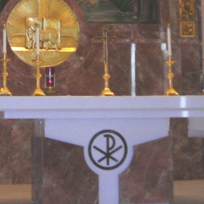 """Going to """"Short Mass."""" Going to daily Mass helps us to grow in our faith. Image of an altar in a Catholic Church covered with a white table cloth with white candles in gold candle holders on it."""