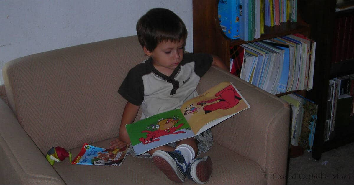 Image of a young boy sitting in chair with ankles crossed looking at a book
