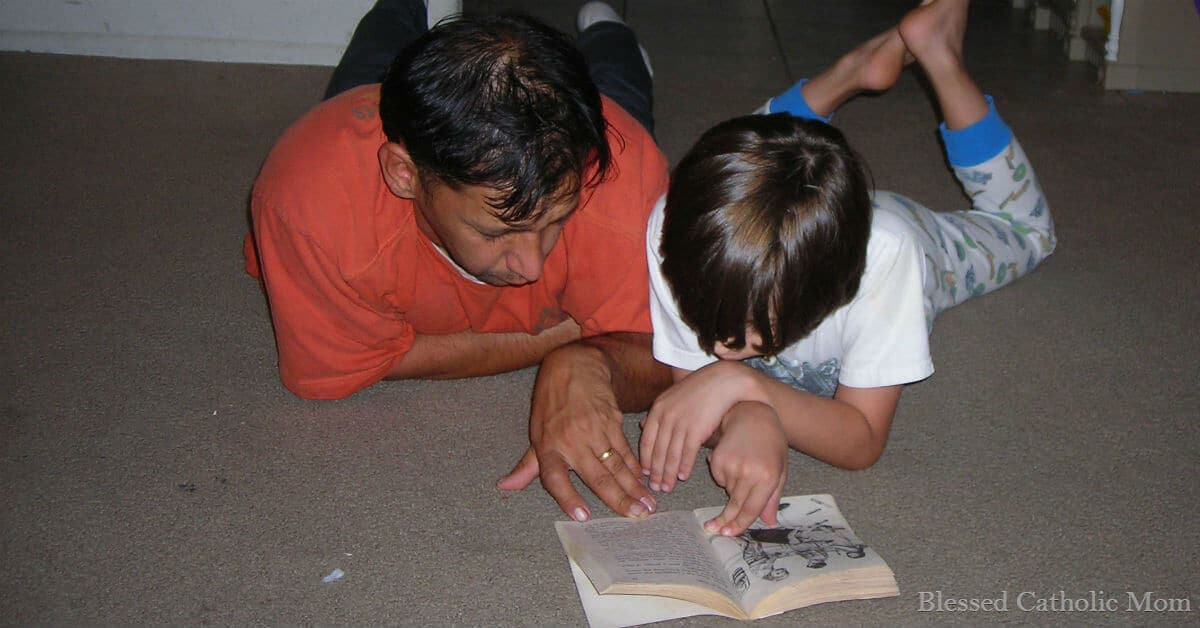 My husband does not babysit our kids; he parents them. Image of a father and son laying on the floor reading together.