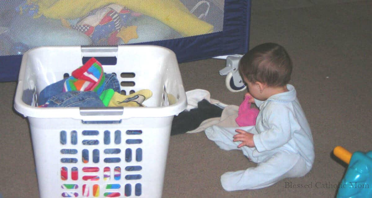 Image of a toddler boy helping unload the laundry basket onto the carpeted floor.