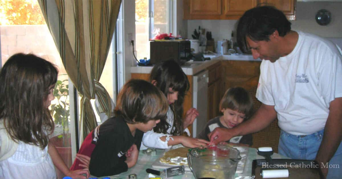 Image of a father around a table with his children making cookies together. Blessed Catholic Mom watermark.