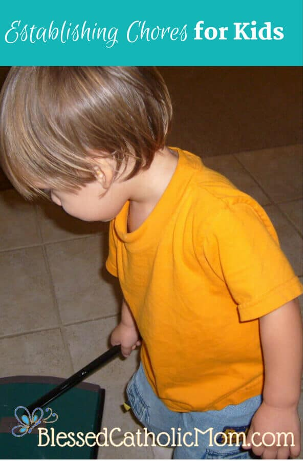 Image of a toddler boy cleaning the kitchen floor with a push vacuum.