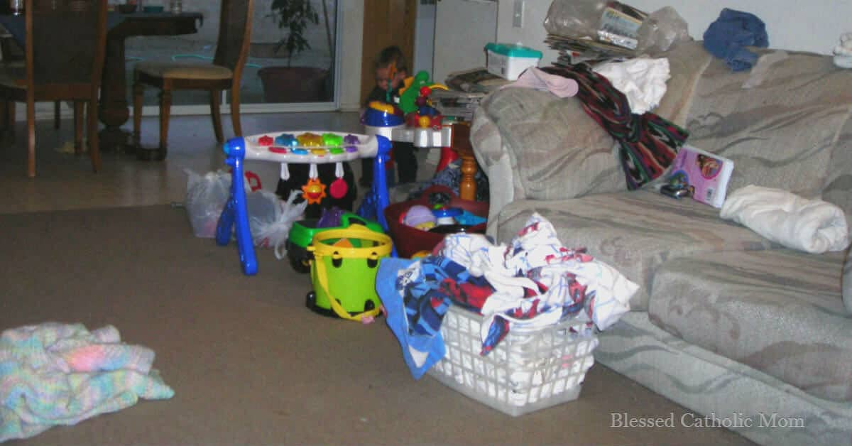Image of a cluttered couch and family room with a basket of laundry and toys beside it.