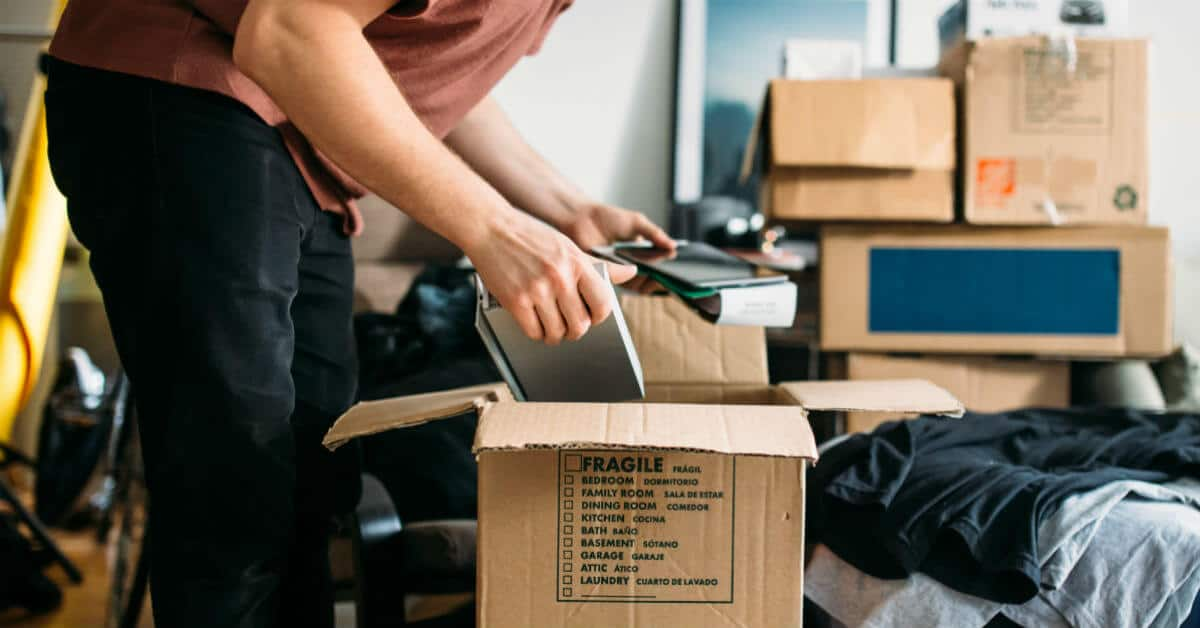 Young man packing a box of items to move out.