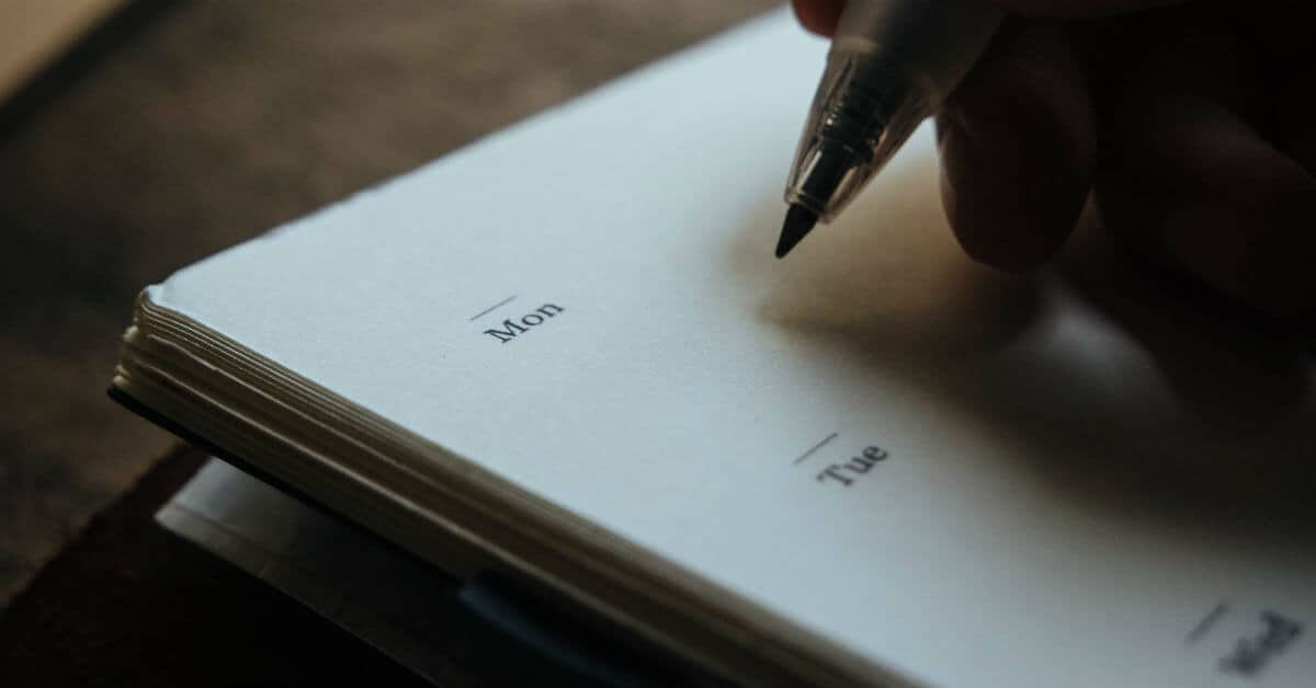 Image of a hand holding a pen about to write down what to do Monday and Tuesday. Image from Death to stock photo.
