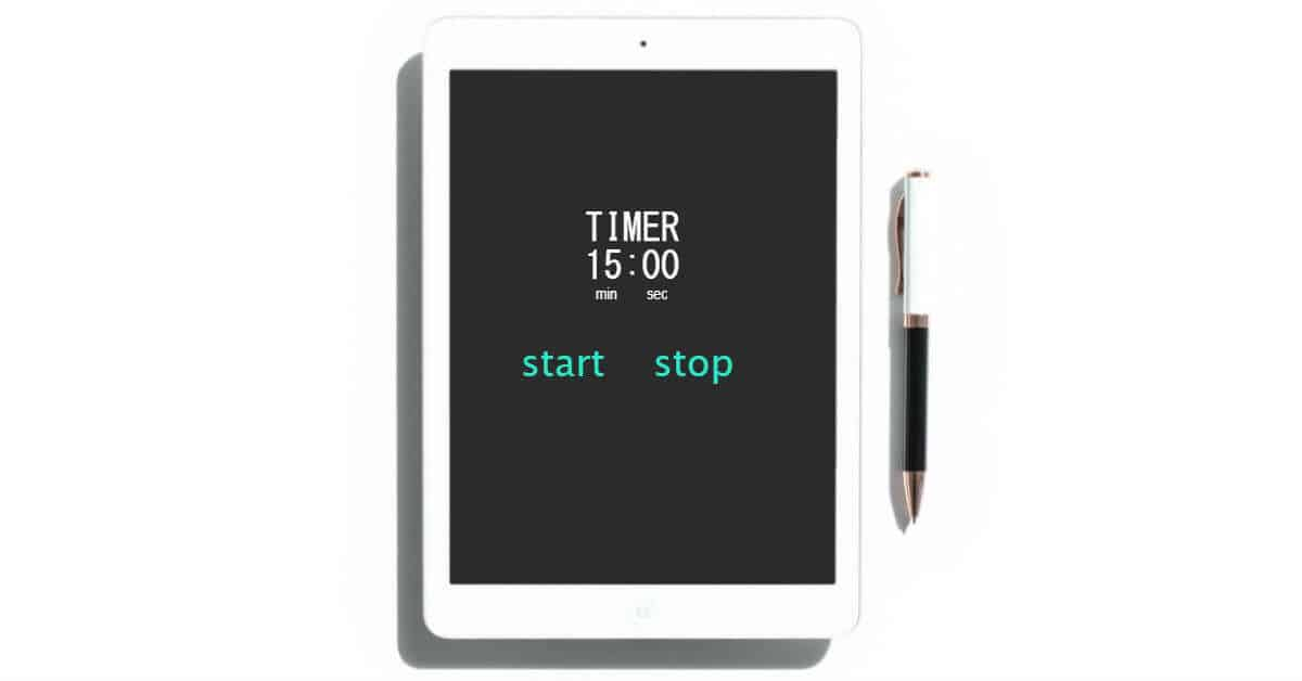 Image of a timer on a table set for 15 minutes. a pen is beside it. Image was modified form a Haute Stock image.