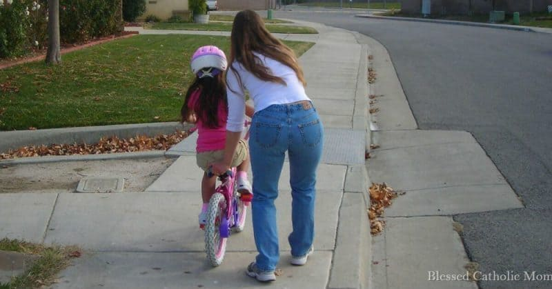 Image of a mom helping daughter ride a bike without training wheels.