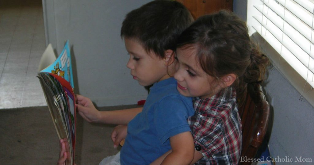 Image of a girl reading to her little brother who is sitting on her lap on a chair.