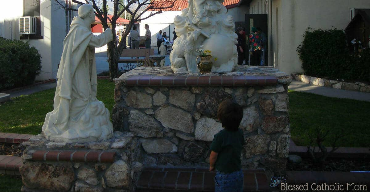 Going to Mass with young children. Image of a boy looking up at statues outside of a Catholic church.