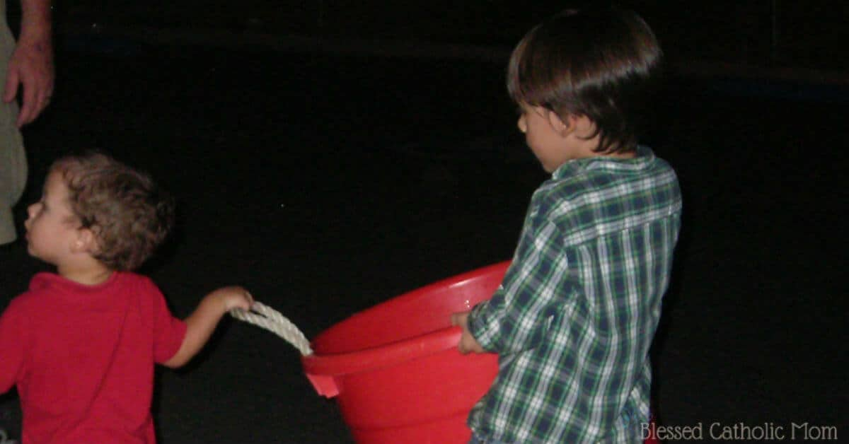 Help at church as a family. Image of two boys carrying a bucket to put it away after a church event.
