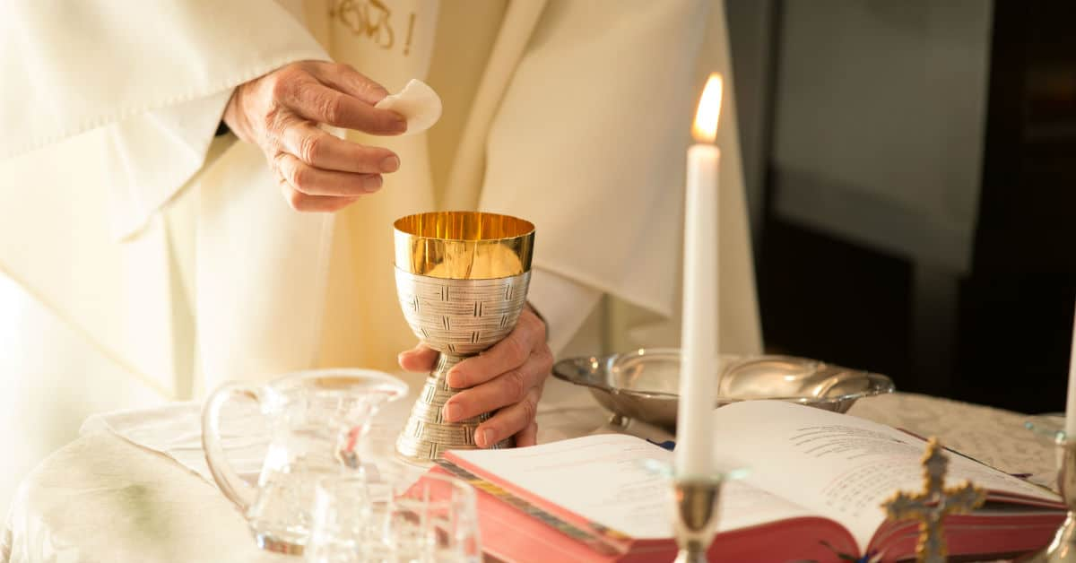 Image of a the hands of a priest as he stands at the altar holding a host and a chalace at Mass.