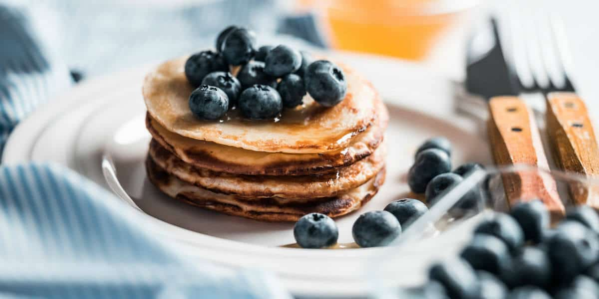 A simple before school routine helps our school day to get started on the right foot. Eat breakfast is step number 3. Image of pancakes with blueberries on top of them. Image from picjumbo.