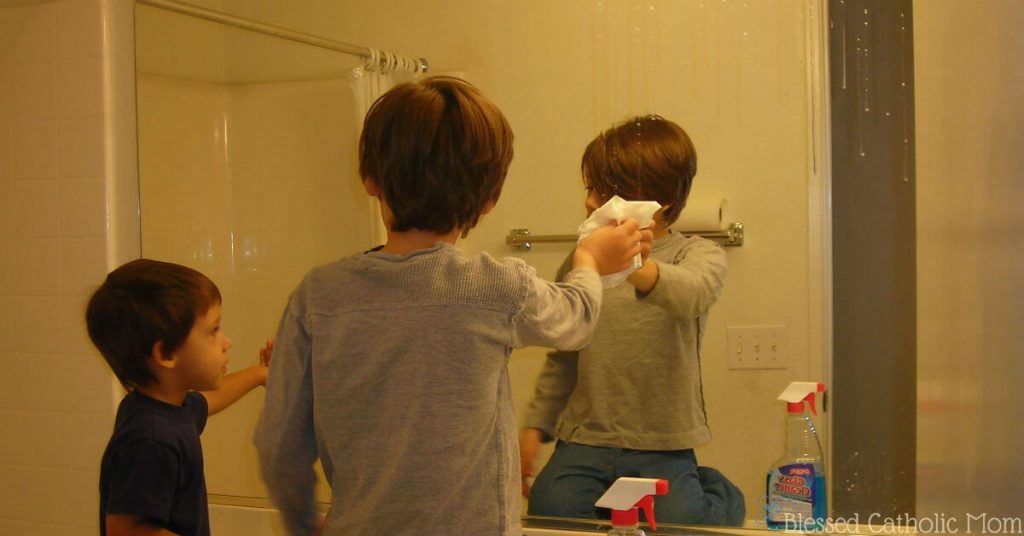Image of a boy cleaning a bathroom mirror while his younger brother looks on.