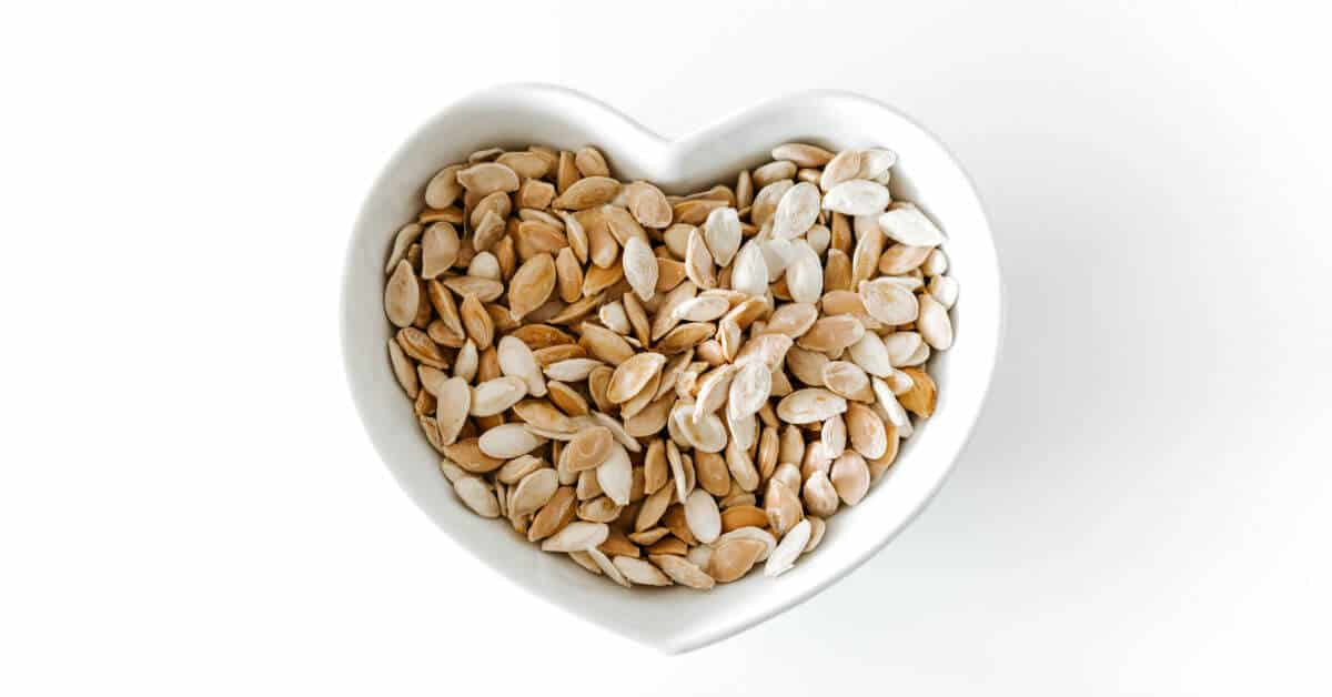 Are you feeling overwhelmed with all that you desire to be for your family, for yourself, and for God? Eating right can help keep these feelings at bay. Image of a heart shaped white bowl filled with roasted pumpkin seeds. Image by picjumbo.
