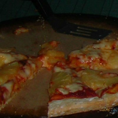 Image of slices of homemade pizza on a baking stone.