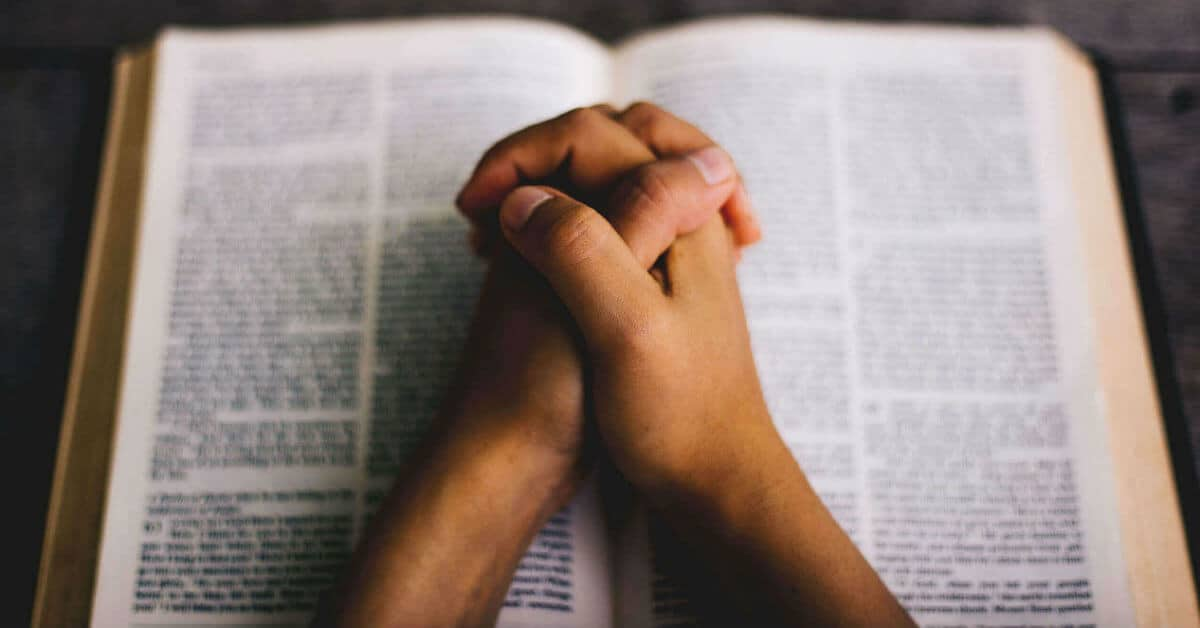 Image of two hands clasped on top of an open Bible.Image form Lightstock images.