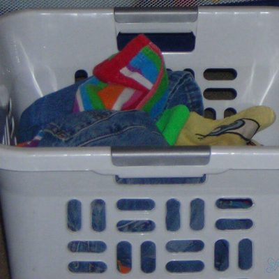Image of a white basket full of laundry. Blessed Catholic Mom logo on image.