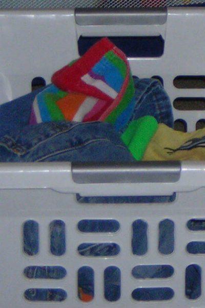 Image of a white basket full of laundry. Blessed Catholic Mom logo on image.