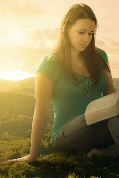 Image of a giant woman sitting by a town reading her Bible.