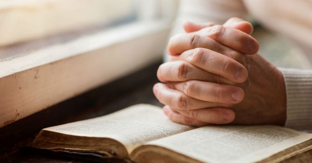 Image of a person sitting by a window, hands clasped together on top of an open Bible.