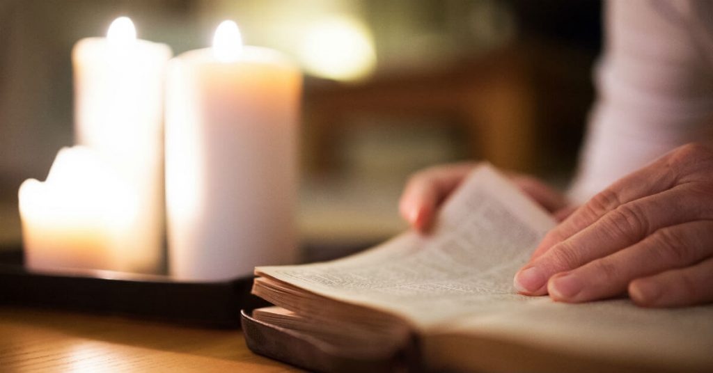 Image of a an open Bible with a hand about to turn the page. A lit candle in the background.
