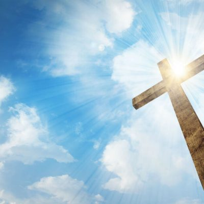 Image of a cross with the sun shining behind it in a blue sky with some white clouds.