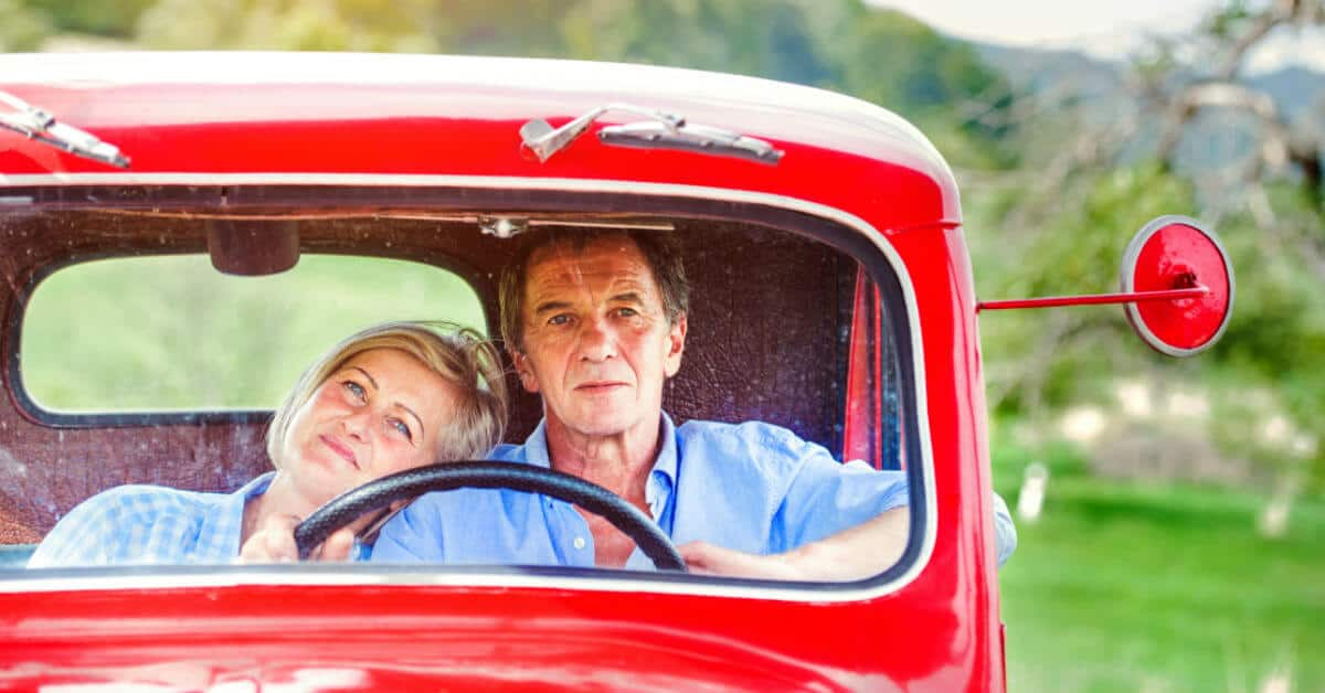 Spend time together doing things you loved doing together in the past. Image of a couple sitting in a truck together. The woman has her head on the man's shoulder.