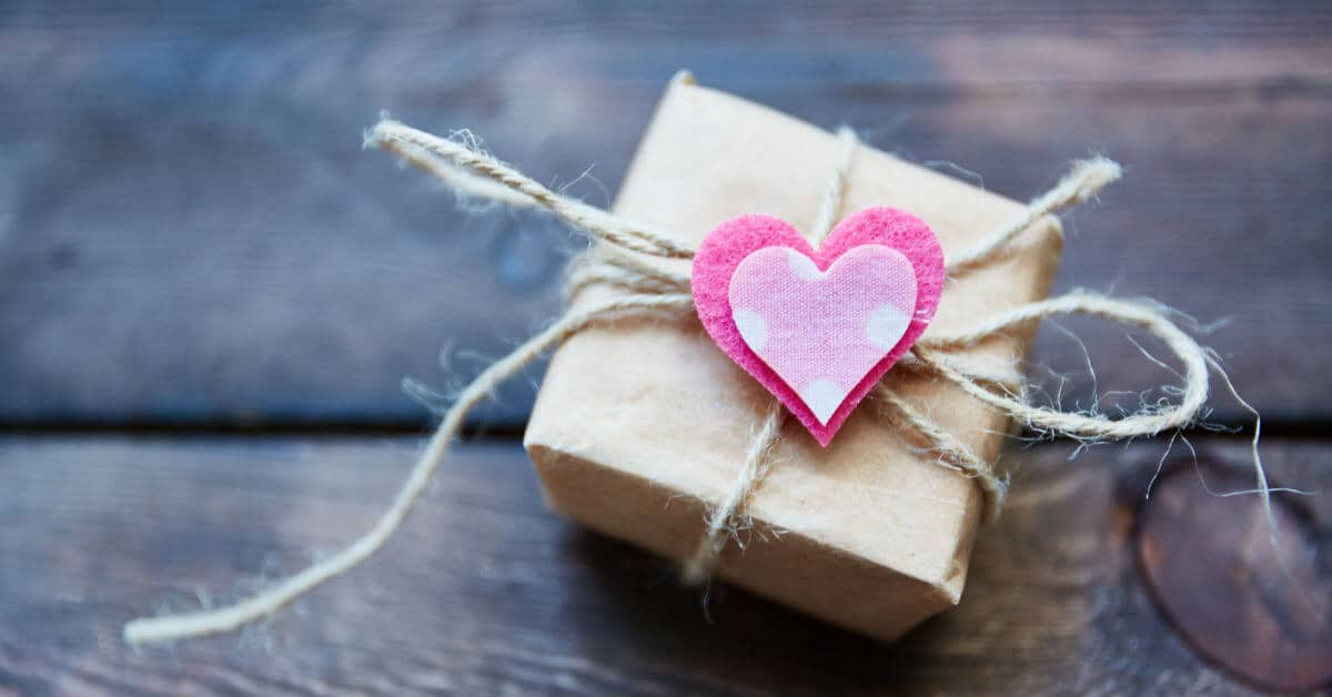 Do little things for your spouse that will bring a smile to his face. Image of a small box wrapped in brown paper and tied with twine with a heart on it.