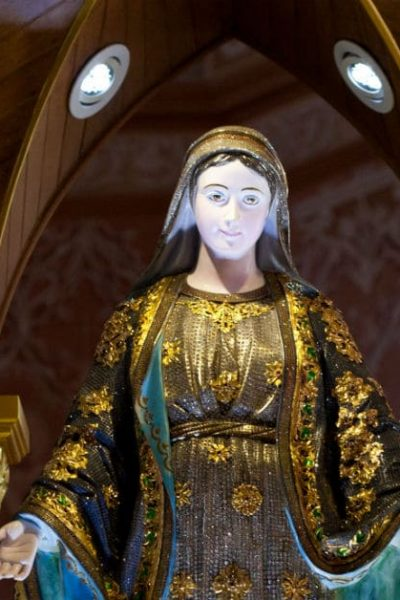 Image of a statue of Mary in a church, her arms outstretched towards us.