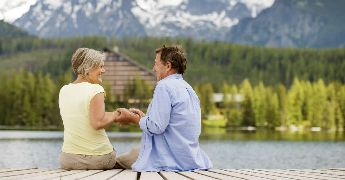 Take the time to really listen to each other. Image of a couple sitting on a dock over the water holding hands, smiling, and looking into each others' eyes.
