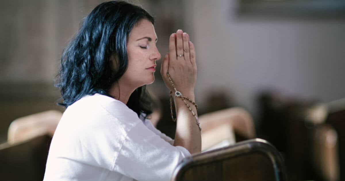 Image of woman holding a Rosary and praying at church.