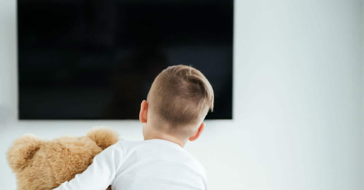 Here are tips to make family dinners happen and enjoyable. Create a special time together to have fun, learn more about each other, and plan together. Turn off the TV when you eat together. Image of a boy holding a teddy bear, sitting facing a TV screen that is off.
