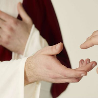 Image of a person representing Jesus holding out his hand to a person who si holding out his hand to Jesus.